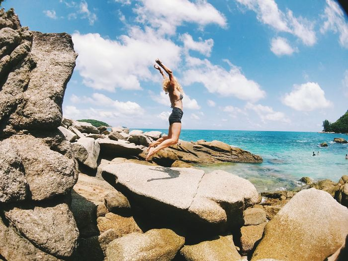 Side view of woman jumping on rock at beach against sky