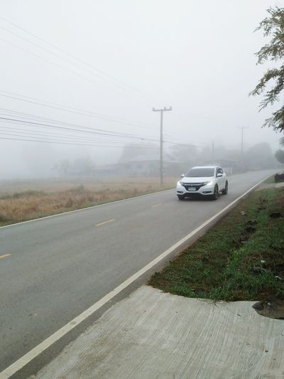 Drive safe on a foggy road Weather Car Fog Rain Torrential Rain Transportation Winter Storm Wind Storm Cloud Social Issues Day No People Traveling Outdoors Cold Temperature Road Photography Themes Nature Sky Car Car On The Road