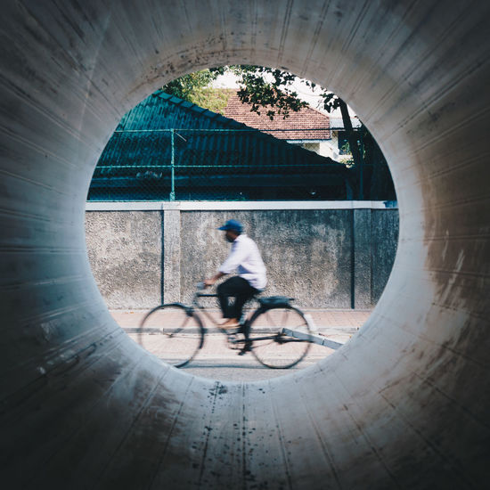 Blurred Motion Of Man Riding Bicycle Seen Through Concrete Pipe Hole