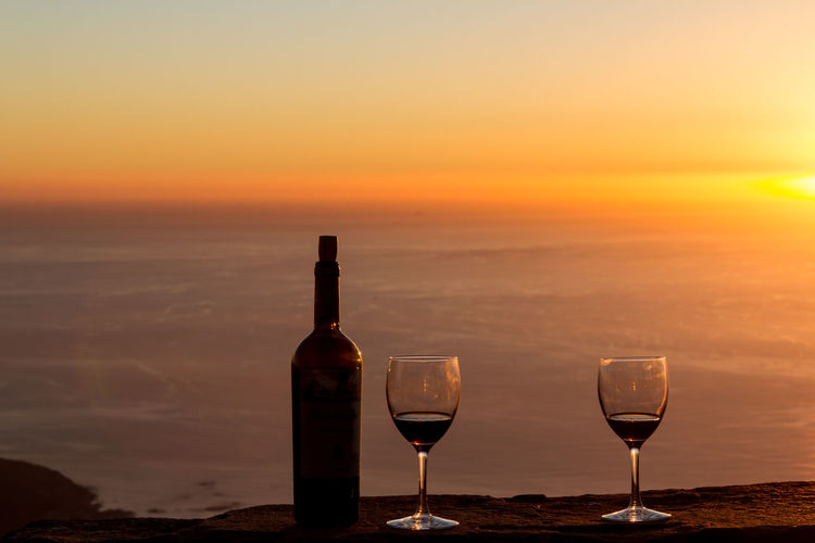 Close-up of wineglasses with bottle on retaining wall against sea during sunset