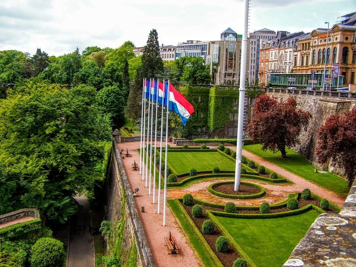 Place de la Constitution in the City of Luxembourg with city and trees Luxembourg Place De La Constitution Architecture Building Building Exterior Built Structure Capital City Cloud - Sky Day Europe Flag Garden Green Color Growth Hedge National Icon Nature No People Outdoors Patriotism Plant Pride Sky Tree