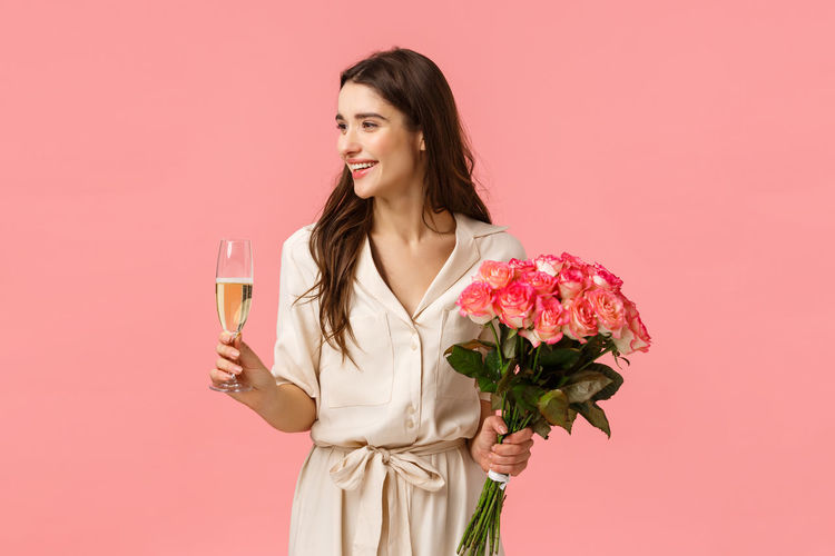 Young woman standing by pink rose against red background