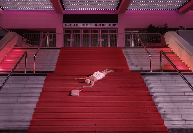 Dead woman on staircase of auditorium at night