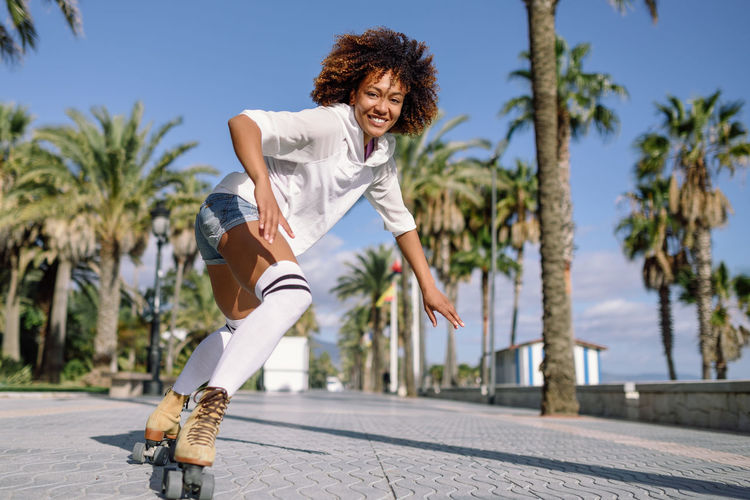 Young fit black woman on roller skates riding outdoors on urban street. Smiling girl with afro hairstyle rollerblading on sunny day Beautiful Woman Casual Clothing Cheerful Happiness Leisure Activity Lifestyles Looking At Camera One Person Outdoors Palm Tree Portrait Real People Road Rollerblading Rollerskating Skate Skategirl Skater Skating Smiling Sunlight Tree Women Young Adult Young Women