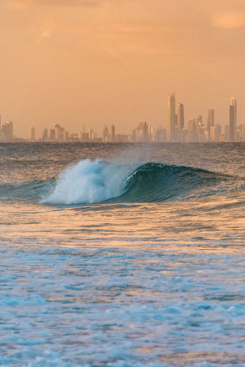 Beautiful big wave with iconic Gold Coast skyscrapers on the background at sunset Sunset Wave Colorful Surf Power In Nature Cityscape Urban Skyline Motion Skyscraper Outdoors Sea Water City