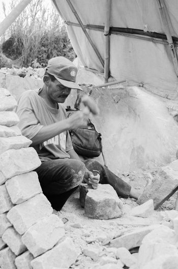 Mason chiseling stone at workshop