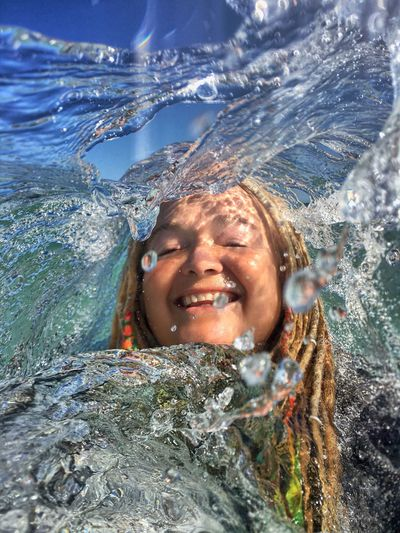 Portrait of smiling young woman swimming in water