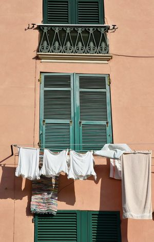 italian house exterior Italian House Building Exterior Hanged Laundry Day Details Genova Liguria,Italy Pastel Colors Pink And Green Window No People Day Hanging Outdoors Architecture