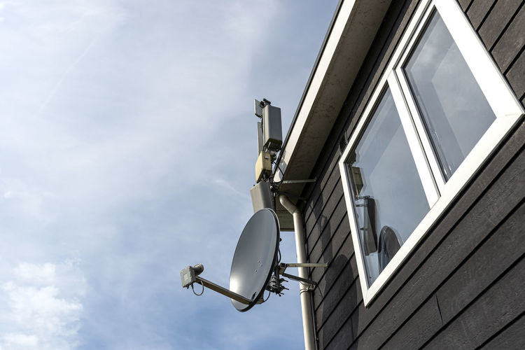 Satellite dish attached to the wooden facade of the house, visible internet and terrestrial tv.