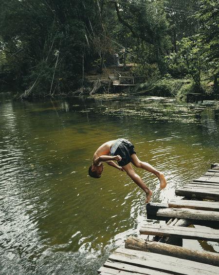 Side view of shirtless man jumping in lake
