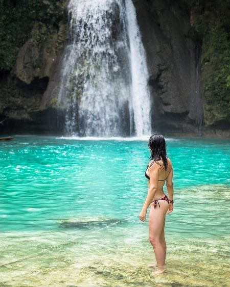 Seductive Woman Standing Against Waterfall At Mountain