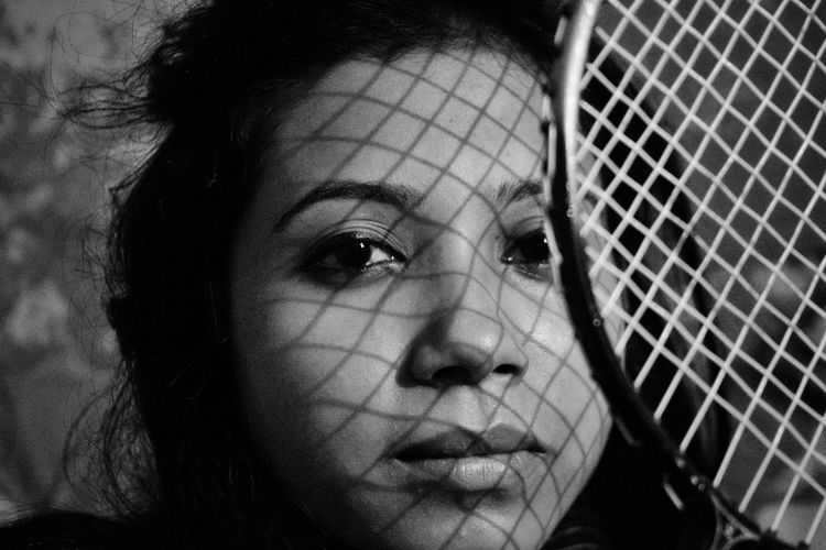 Close-Up Portrait Of Woman With Tennis Racket