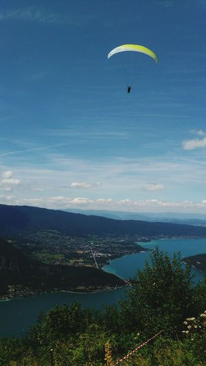 Paragliding over annecy lake against blue sky on sunny day