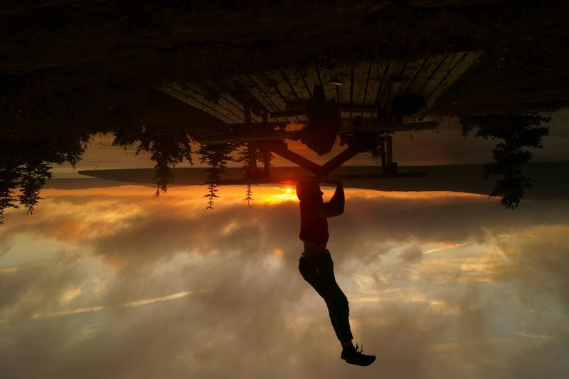 Upside down image of man performing headstand on table against lake during sunset