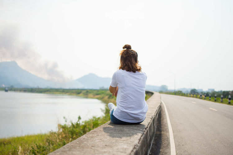 Alone Adult Beauty In Nature Casual Clothing Clear Sky Day Focus On Foreground Full Length Lake Leisure Activity Lifestyles Mountain Nature One Person Outdoors People Real People Rear View Sad Scenics Sitting Sky Tree Women Young Adult