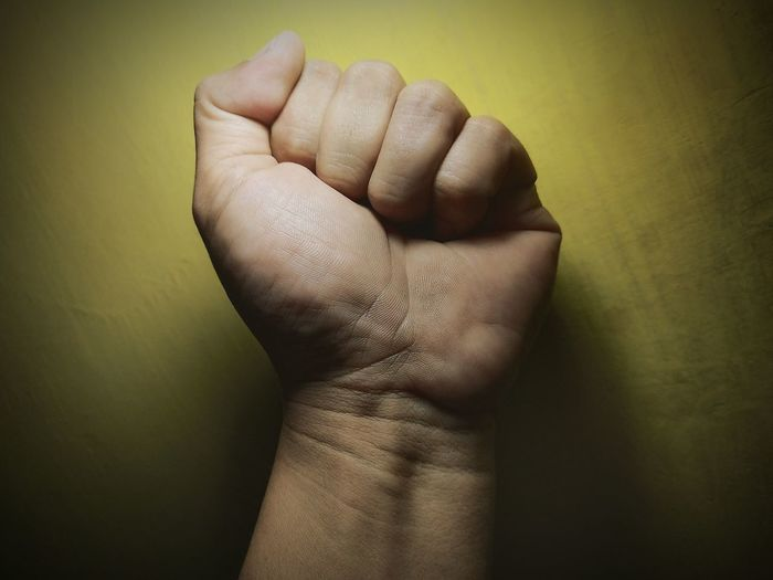 Cropped hand clenching fist against wall