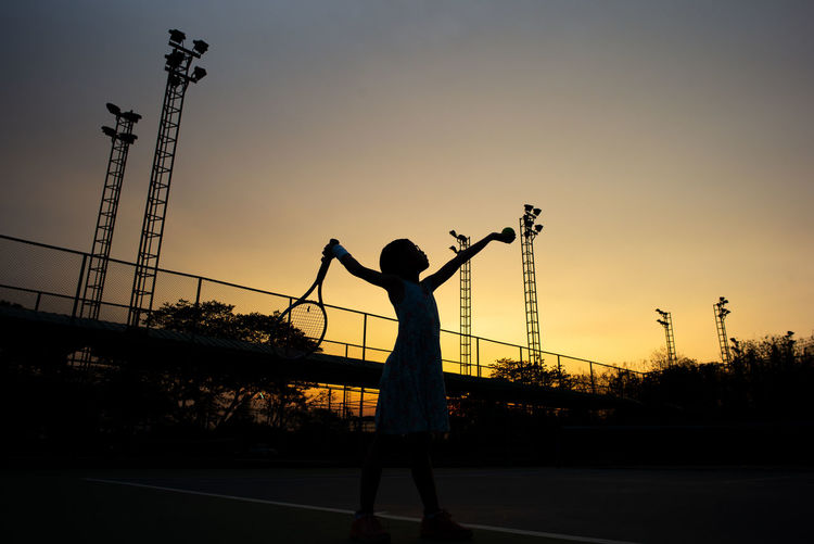 Silhouette portrait of Asian girl plays tennis at outdoor court with sunset sky in background Human Arm Side View Women Holding Orange Color Silhouette Real People Sunset One Person Sky Lifestyles Standing Leisure Activity Outdoors Clear Sky Tenerife Ball Playing Sport Healthy Eating Girl Portrait Shadow Twilight Spotlights Structure Posing Gesture Service Tournament Competition Practice Training First Eyeem Photo Concentration Young Adult Eyeglasses
