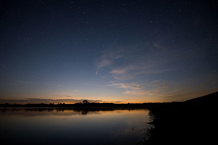 Scenic view of lake against sky at night with neowise comet