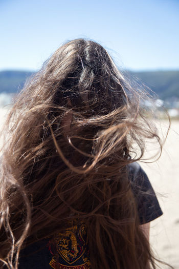 Portrait of brunette girl with long flying hair in the wind outdoors. Young casual woman with wavy hair covering her face. Teenage girl with messy windy tousy blowsy hair. Long Hair Hairstyle Hair Brown Hair One Person Women Portrait Wind Headshot Tousled Hair Day Human Hair Nature Outdoors Teenager Clutter Joyful Carefree Jumble Chaos Disorder Windy Beach Leisure Activity
