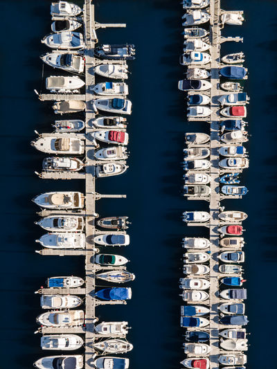 Aerial view of sailboats moored in sea against buildings in city