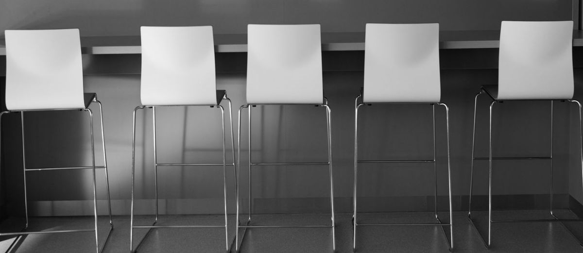 Close-Up Of Chairs Arranging Against Wall