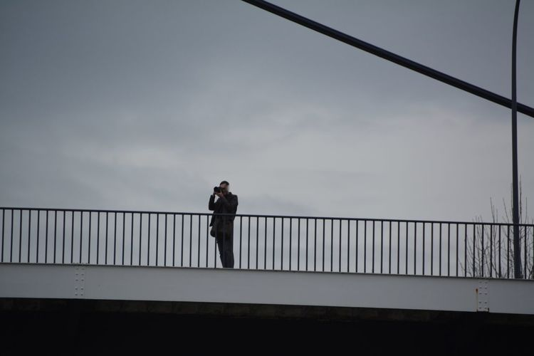 Low Angle View Of Man Photographing Through Slr Camera On Bridge Against Sky