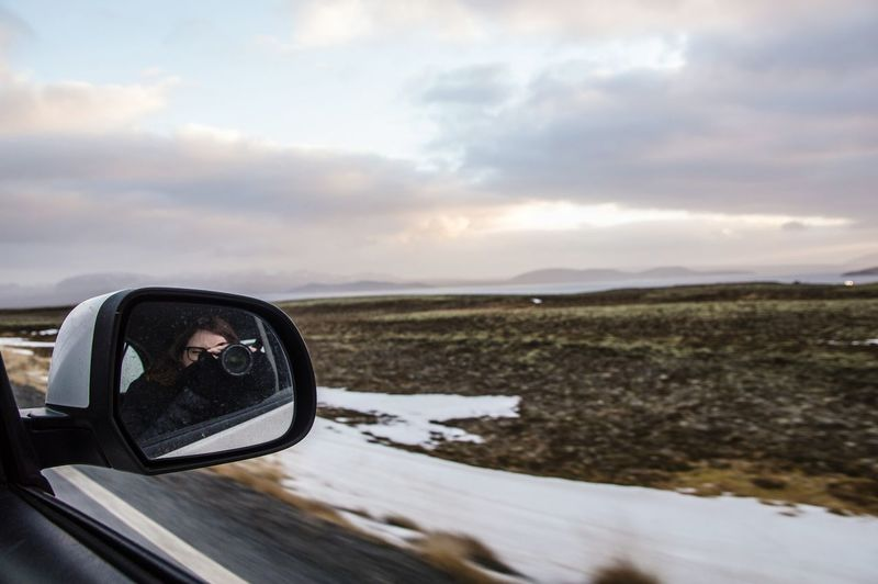 Reflection Of Woman Photographing Through Camera In Side-View Mirror Of Car