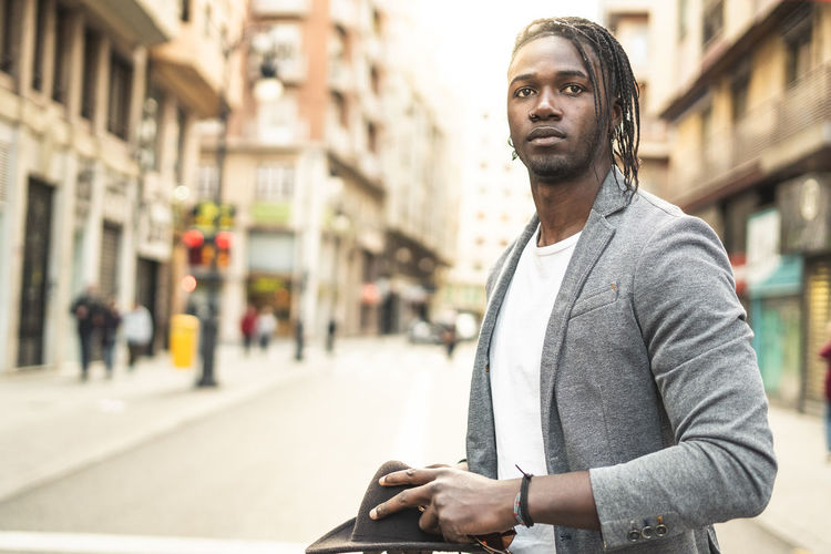 Portrait of young man looking away on street in city