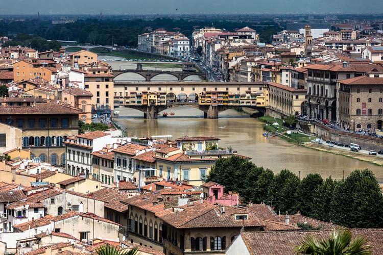 Ponte vecchio over arno river amidst town