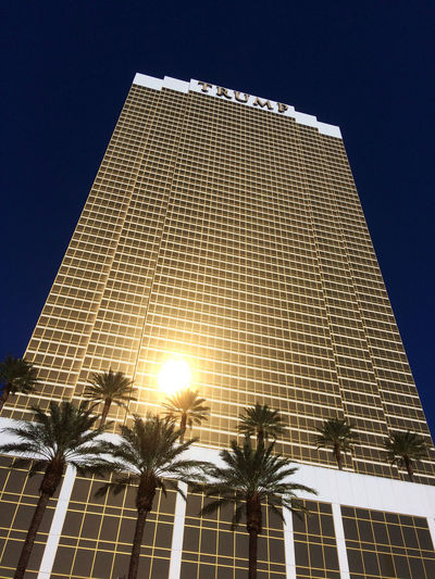 Las Vegas, NV, USA – November 13, 2016: Exterior shot of the Trump International Hotel in Las Vegas. Las Vegas Trump Hotel Architecture Building Building Exterior Built Structure City Clear Sky Hotel Illuminated Low Angle View Modern Nature No People Office Building Exterior Outdoors Palm Tree Plant Sky Skyscraper Sunlight Tall - High Tree Tropical Climate Trump