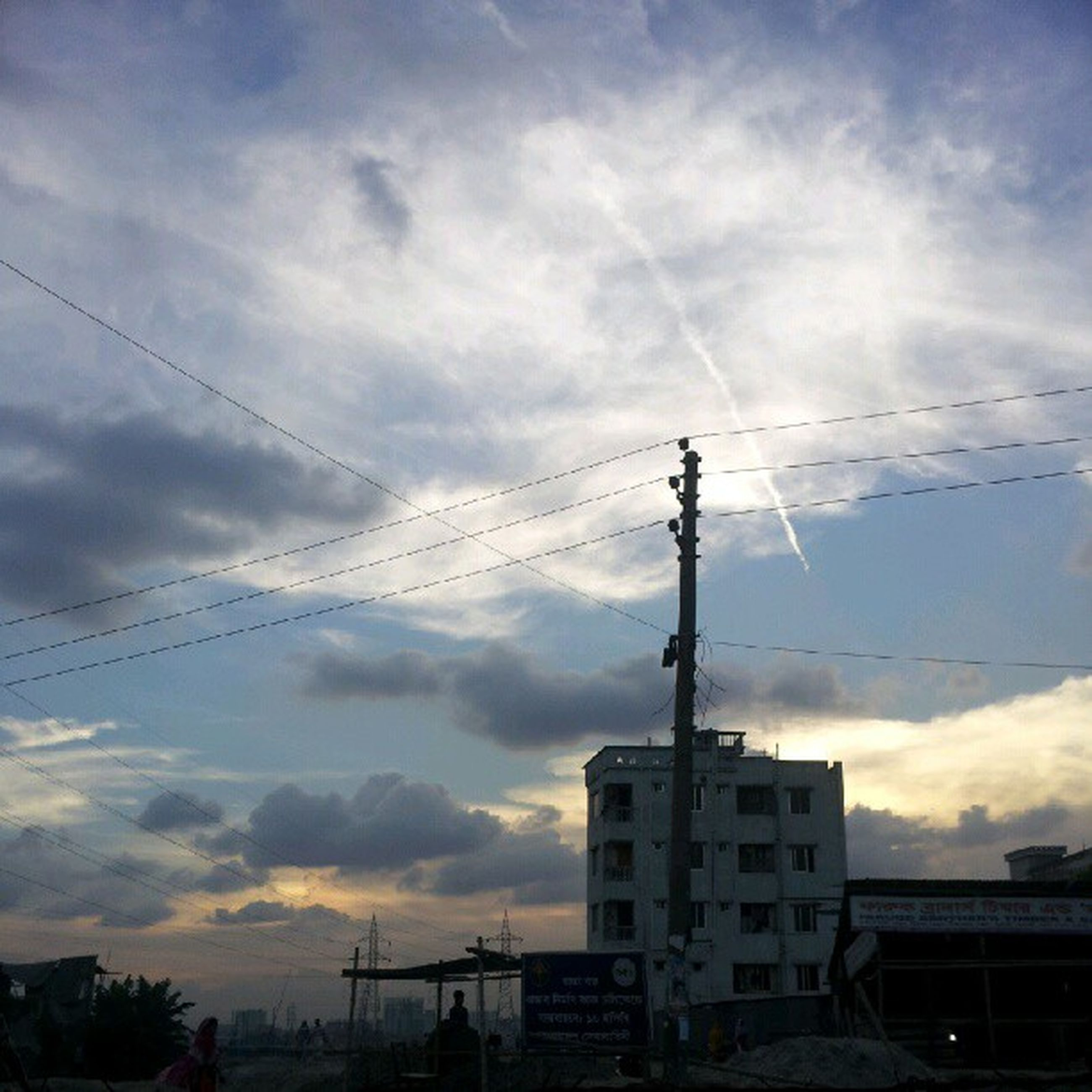 power line, electricity pylon, sky, electricity, cloud - sky, cable, power supply, connection, building exterior, cloudy, fuel and power generation, built structure, architecture, low angle view, silhouette, cloud, technology, sunset, power cable, weather