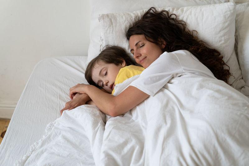 Friends sleeping on bed