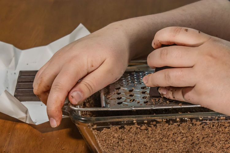 Cropped hands woman grating chocolate in container while sitting at home