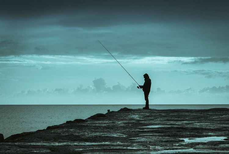 Side view of a man fishing at sea