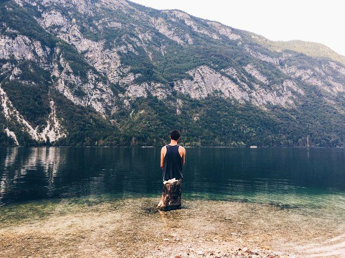 Full length of man standing on lake against mountain