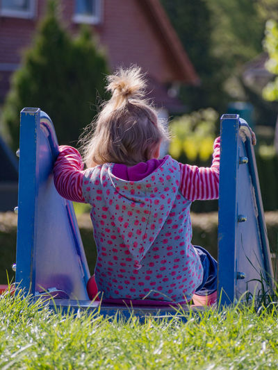 Rear view of girl sitting on slide at playground