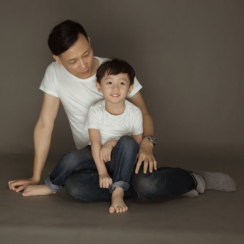 Smiling cute boy sitting on lap of father