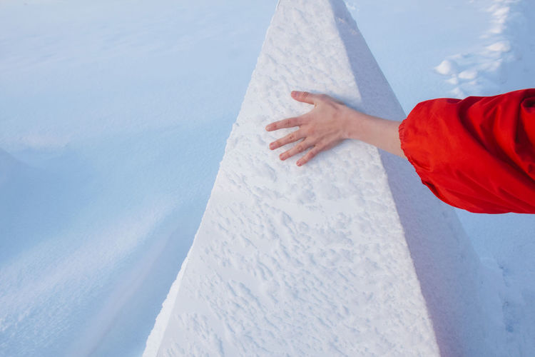 Cropped Hand Of Woman Touching Snow Covered Retaining Wall