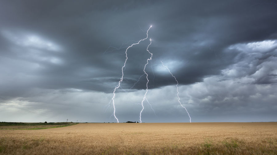 Lightning over field against sky