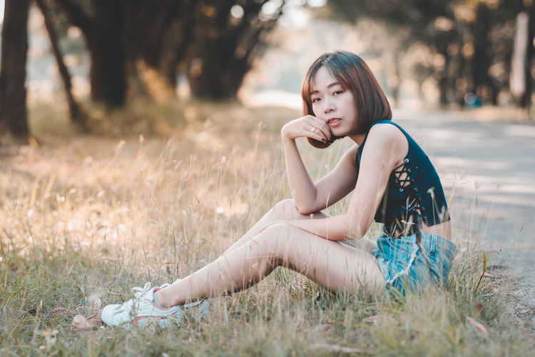 Asian Girl Asian Teen Beautiful Woman Beauty Casual Clothing Fashion Full Length Grass Hairstyle Land Leisure Activity Lifestyles One Person Outdoors Portrait Real People Sitting Teenager Young Adult Young Women