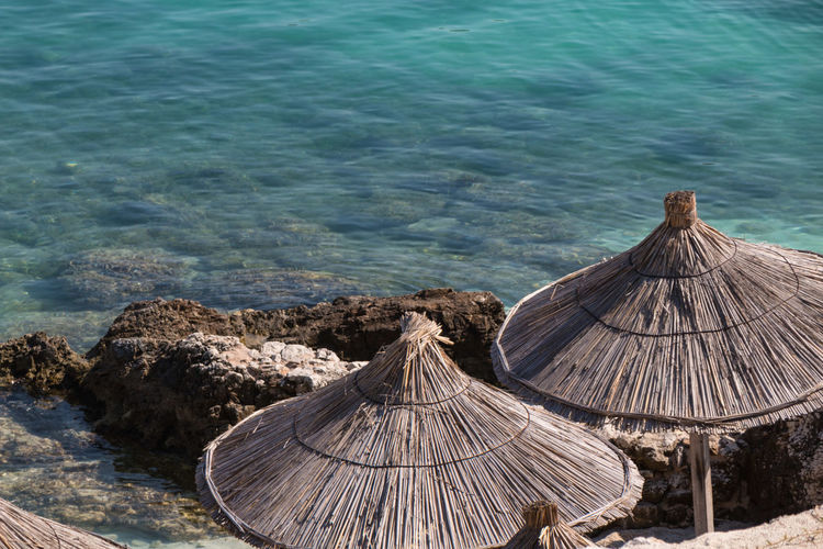 High angle view of parasol on land by sea