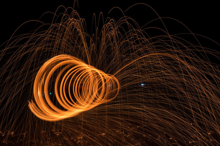 Illuminated wire wool spinning against sky at night