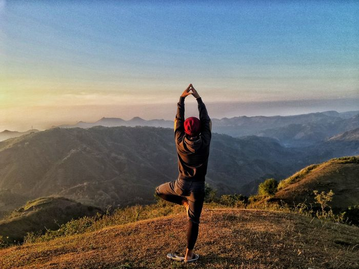 Rear View Of Man Doing Yoga Pose On Mountain