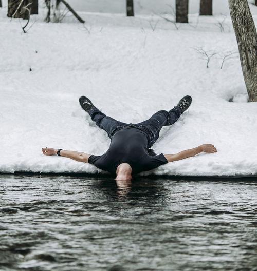 Full length of man lying in snow
