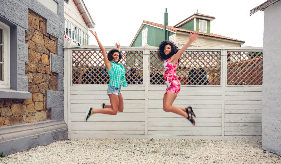 Portrait Of Friends With Arms Raised Jumping On Sand