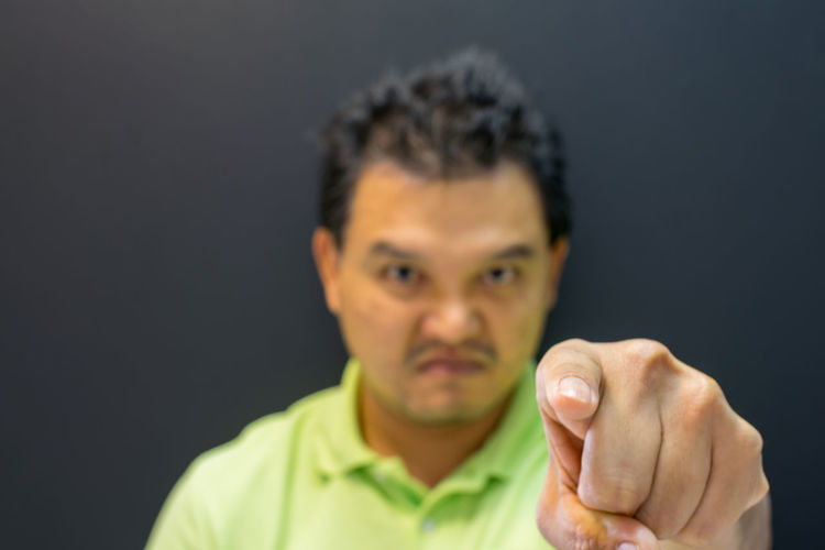 Portrait of angry man pointing against black background