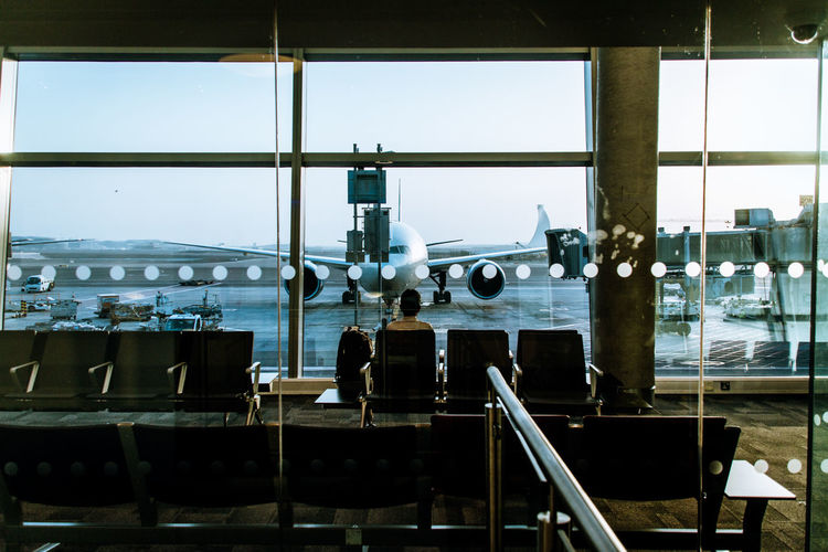 Man Sitting In Waiting Area Of Airport And Overlooking Aircraft Through Glass Window