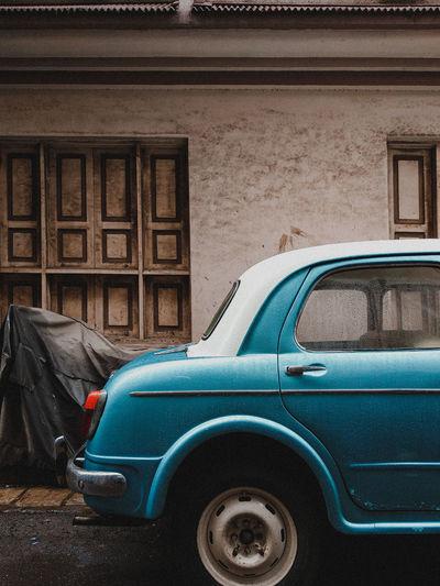 Old car on street against buildings in city
