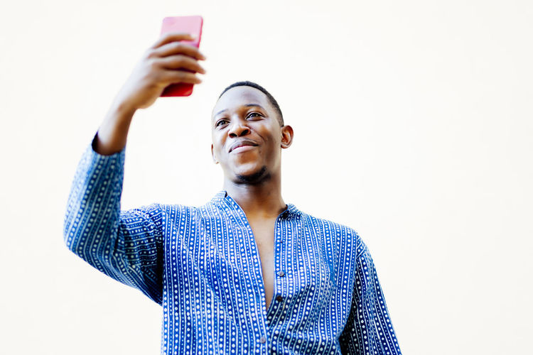 Portrait of smiling man photographing while using smart phone against clear sky