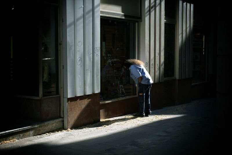 Reflection of man on door of building